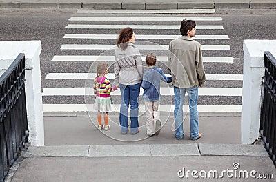 Family standing near crosswalk, behind