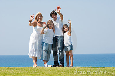 Family standing outdoors waving