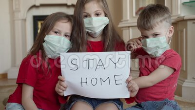 Family stay at home concept. Three children in mask holding sign saying stay at home for virus protection and take care stock video footage