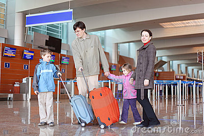 Family with suitcases in airport hall