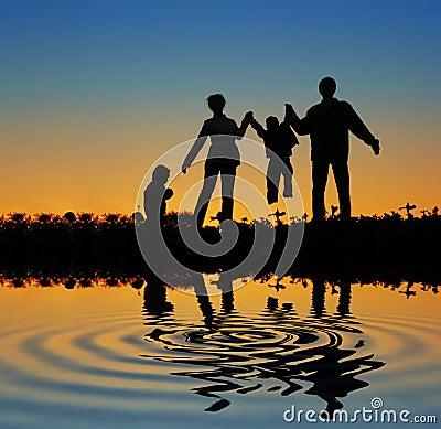 Family on sunset pond