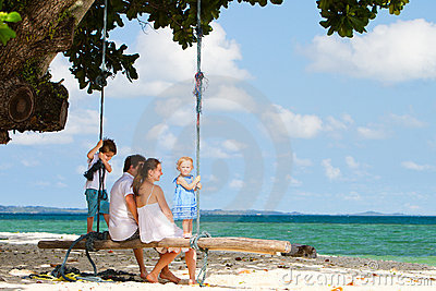 Family swinging on tropical beach