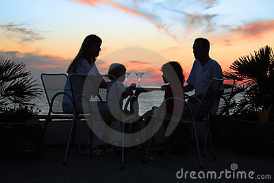 Family at table on beach on sunset