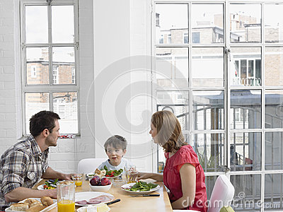 Family Of Three Having Meal At Dining Table