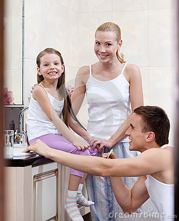 Family of three people brush their dents