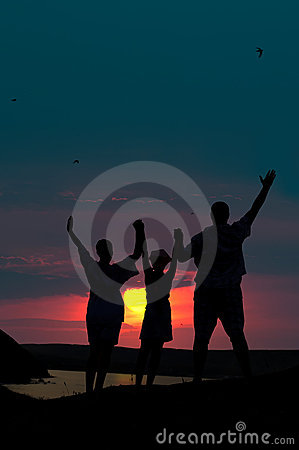 The family from three persons welcomes the sunset