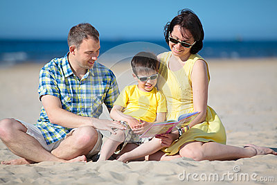 Family of three reading book on beach