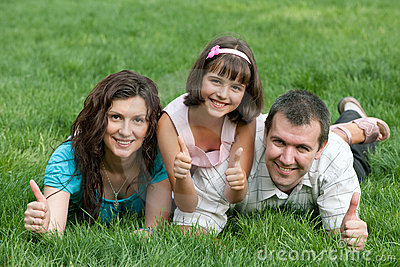 Family of three with thumbs up in the park