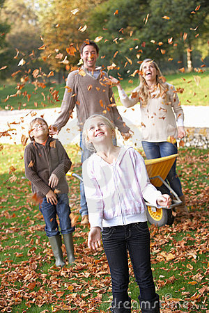 Family throwing autumn leaves into the air