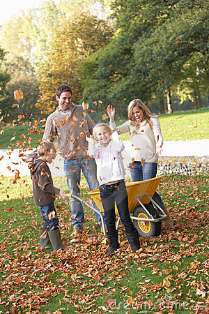 Free Family Throwing Autumn Leaves Into The Air Royalty Free Stock Image - 18044036
