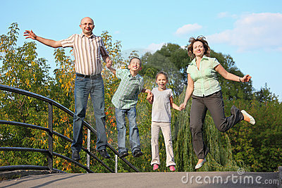 Family with two children is jumping on a bridge