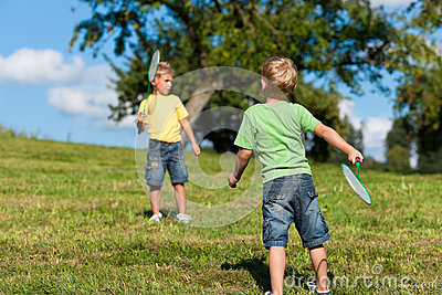 Family - two little boys playing badminton outdoor