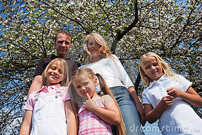 Family under apple tree in spring