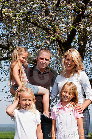 Family under apple tree in spring