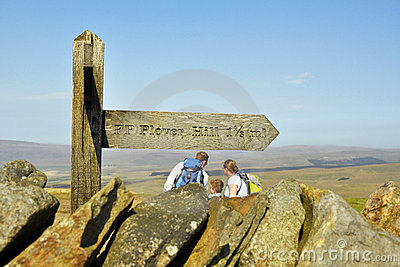 Family under signpost on top of hill