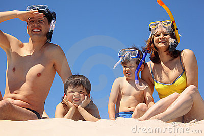 Family in underwater masks sit on sand