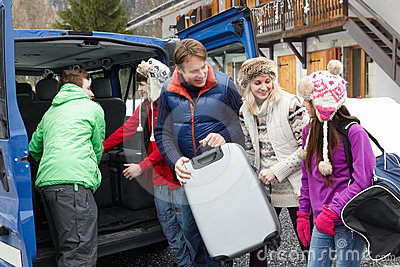 Family Unloading Luggage From Van Outside Chalet