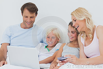 Family using computer and credit card in bed