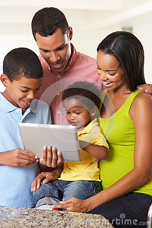 Family Using Digital Tablet In Kitchen Together