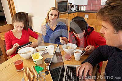 Family Using Gadgets Whilst Eating Breakfast
