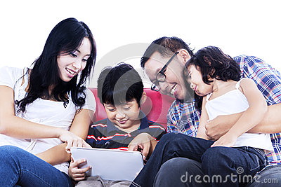 Family using touchpad on red sofa - isolated