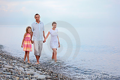 Family walk on beach in evening, focus on mother