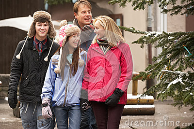 Family Walking Along Town Street In Ski Resort