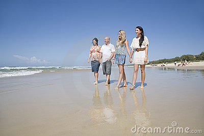 Family walking on beach holding hands