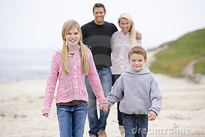 Family walking at beach holding hands