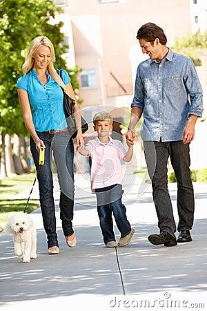 Family walking dog in city street