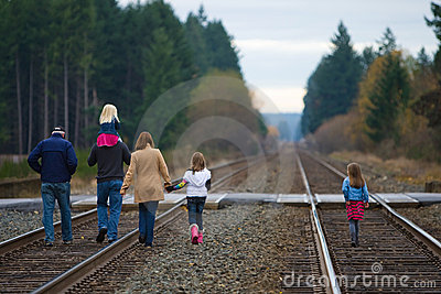 Family walking down train tracks