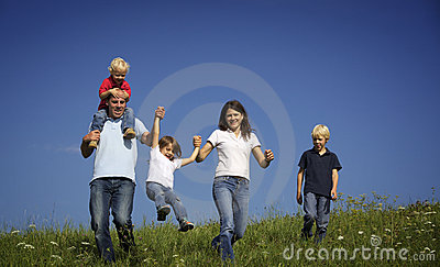 Family walking in field playing with children
