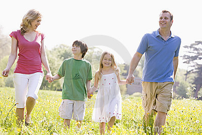Family walking outdoors holding flower smiling