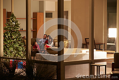 Family Watching Christmas TV At Home Viewed From O