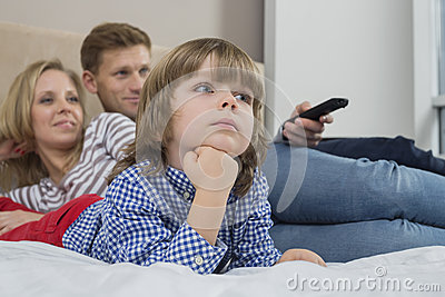 Family watching TV in bedroom