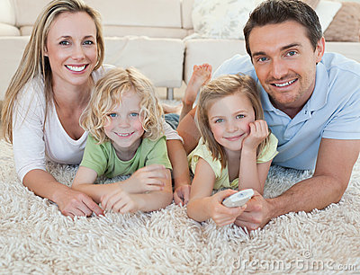 Family watching tv on the floor