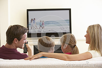Family Watching Widescreen TV At Home Stock Photo