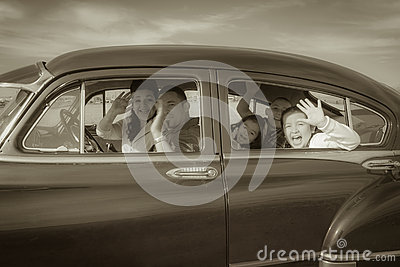 Family Waving Hello in Vintage Car