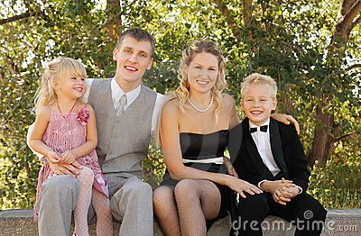 Family wearing holiday clothes sit and smile