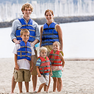 Family wearing life jackets at beach