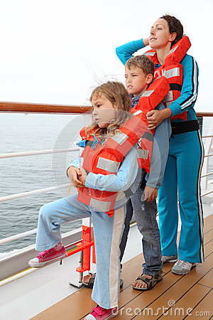Family wearing in life jackets stand at deck
