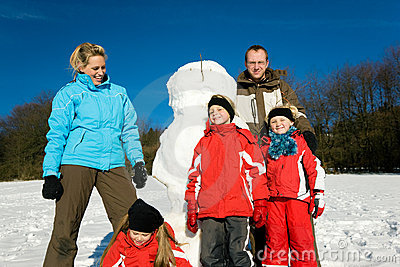 Family in winter standing in front of their snowma