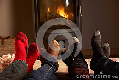 Familys Feet Relaxing By Cosy Log Fire