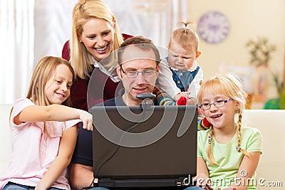 Família com o computador que tem a videoconferência