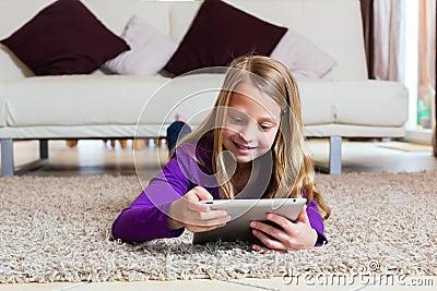 Família - criança que joga com a almofada do computador da tabuleta