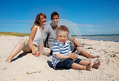 Família da raça misturada que olha feliz na praia