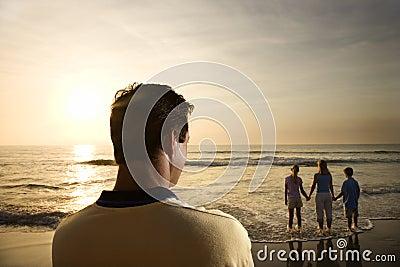 Família de observação do homem na praia
