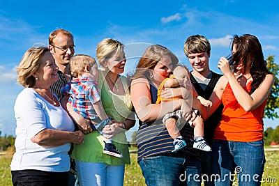 Família e multi-geração - divertimento no prado no verão
