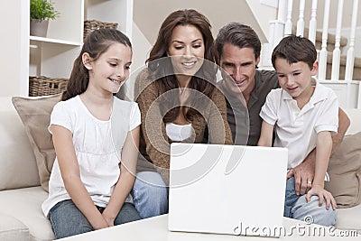 Família feliz que usa o computador portátil no sofá em casa