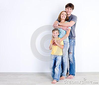 Família no abraço perto da parede